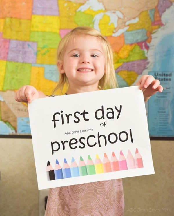 "Preschool girl hold a ""first day of ABCJesusLovesMe preschool""  sign."