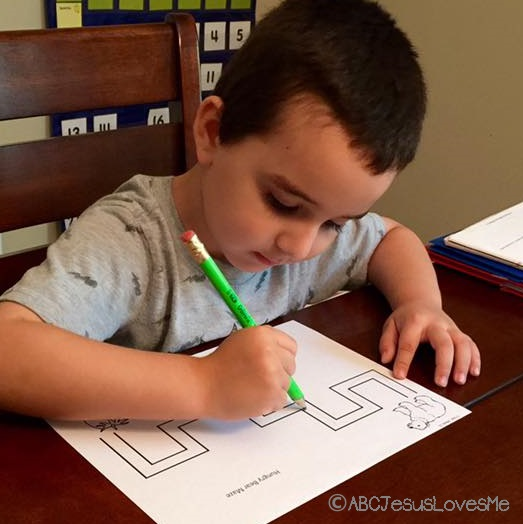 Preschooler doing a maze worksheet.