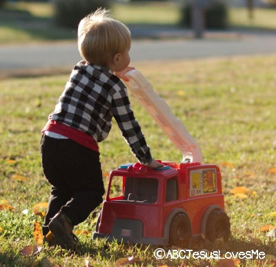 Preschool boy playing outside with firetruck.