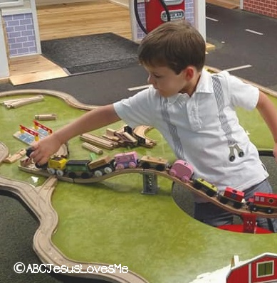 Preschooler playing with wooden trains.